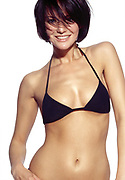 Happy woman standing in front of a white background wearing a black bikini