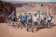 SHOT 10/14/16 2:04:28 PM - Group picture before riding the White Rim Trail. The White Rim is a mountain biking trip in Canyonlands National Park just outside of Moab, Utah. The White Rim Road is a 71.2-mile-long unpaved four-wheel drive road that traverses the top of the White Rim Sandstone formation below the Island in the Sky mesa of Canyonlands National Park in southern Utah in the United States. The road was constructed in the 1950s by the Atomic Energy Commission to provide access for individual prospectors intent on mining uranium deposits for use in nuclear weapons production during the Cold War. Four-wheel drive vehicles and mountain bikes are the most common modes of transport though horseback riding and hiking are also permitted.<br /> (Photo by Marc Piscotty / © 2016)