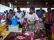 08 OCTOBER 2017 - NEGOMBO, WESTERN PROVINCE, SRI LANKA: A fish monger cuts up a fish for a customer in a fish market in Negombo, north of Colombo. Fish is an important source of protein for many Sri Lankans.    PHOTO BY JACK KURTZ