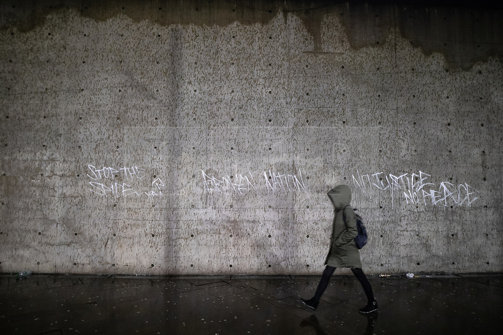 """© Licensed to London News Pictures . 21/12/2018 . Manchester , UK . A woman walks past architect Tadao Ando's concrete wall in Piccadilly Gardens , which has had the words """" Stop the Spice """", """" Broken Nation """" and """" No Justice No Peace """" painted across it . Mad Friday in Manchester City Centre - named for historically being one of the busiest nights of the year for the emergency services in the UK  . Photo credit : Joel Goodman/LNP"""
