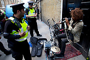 Busker Lewis Floyd Henry playing his music on Brick Lane in the East End of London. He is a well known and quite brilliant performing his blues based busking music. Here he is being stopped by police for breaking the law after he was earlier asked to move on. Must to the anger of gathered people, he was given a fine and sent on his way.