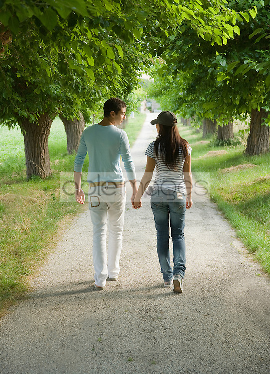 Young couple walking holding hands