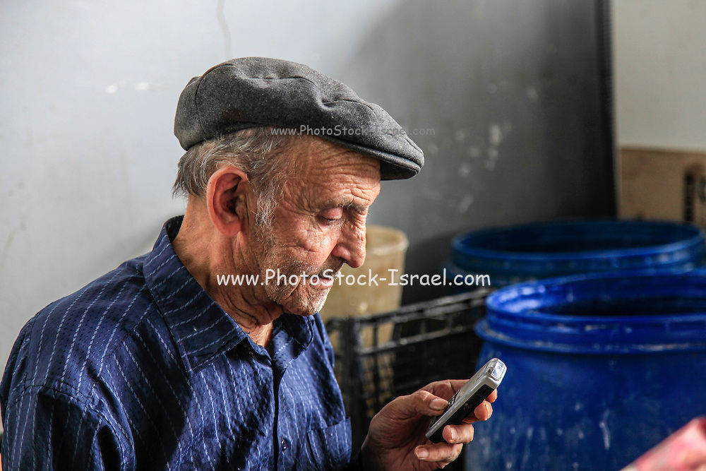 Old mature man uses a cellphone in the market, Yerevan, Armenia
