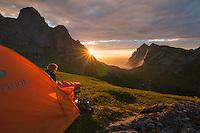 Female hiker watches sunset over Bunes beach from outside tent, Moskenesøy, Lofoten Islands, Norway
