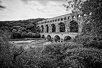 Black and white view of Pont du Gard (Roman Aqueduct), the second highest standing Roman structure, and built in 19 BC above the Gardon River, Vers-Pont-du-Gard, France.