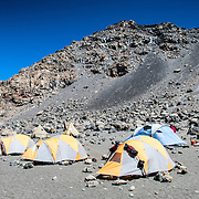 Tents set up on the dirt and rocks at Crater Camp (18,810 feet), with Kibo Summit behind on Mt Kilimanjaro.