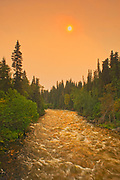 The Grass River and late afternoon sun with fire smoke in the air<br />Pisew Falls Provincial Park<br />Manitoba<br />Canada