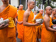 08 SEPTEMBER 2013 - BANGKOK, THAILAND:  Buddhist monks wait to cross a Bangkok street after a mass alms giving ceremony in Bangkok Sunday. 10,000 Buddhist monks participated in a mass alms giving ceremony on Rajadamri Road in front of Central World shopping mall in Bangkok. The alms giving was to benefit disaster victims in Thailand and assist Buddhist temples in the insurgency wracked southern provinces of Thailand.     PHOTO BY JACK KURTZ