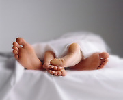 Couples feet intertwined and under the sheets in bed