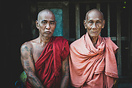 Mandalay, Myanmar - Novmber 9, 2011: Two Burmese monks in their 70s standing together on the porch of their monastery in Mandalay, Myanmar.