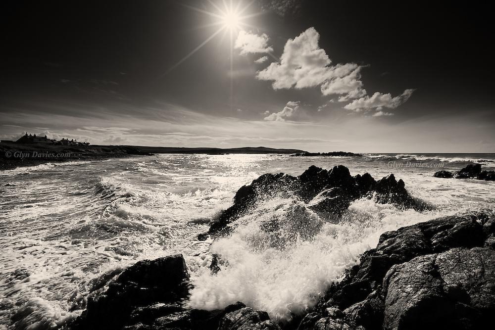 Brilliant morning sunshine backlighting crashing waves at Porth Tyn Tywyn, West Anglesey, North Wales.