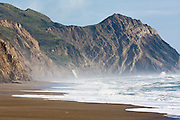 Alamere Falls and steep uplifted cliffs are visible in the distance as waves roll gently onto sandy Wildcat Beach,  Point Reyes National Seashore, California.