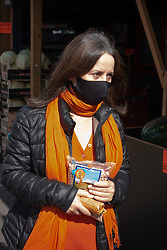 Woman shopping at a food shop in Reading wearing a face mask during Coronavirus lockdown, UK. model released.