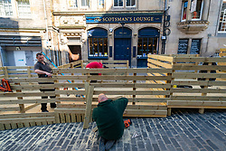 Edinburgh, Scotland, UK. 25 April 2021. Scenes from streets of Edinburgh city centre on Sunday afternoon on the day before non-essential shops and businesses can reopen in Scotland under relaxed covid-19 lockdown rules. Pic. Joiners making finishing touches to a redesigned outside seating platform at The Scotsman's Lounge on Cockburn Street.The original single level platform did not meet building control rules and a stepped design has now been built. Iain Masterton/Alamy Live News