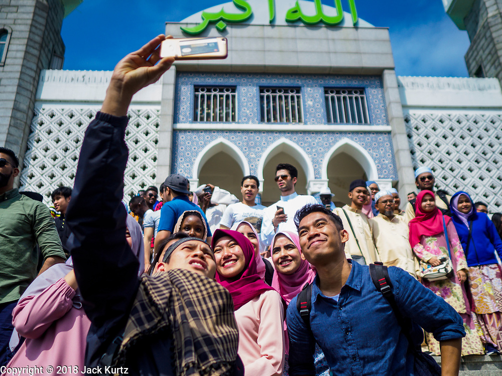 """15 JUNE 2018 - SEOUL, SOUTH KOREA: Muslims from Indonesia pose for """"selfies"""" at Seoul Central Mosque on Eid al Fitr, the Muslim Holy Day that marks the end of the Holy Month of Ramadan. There are fewer than 100,000 Korean Muslims, but there is a large community of Muslim immigrants in South Korea, most in Seoul. Thousands of people attend Eid services at Seoul Central Mosque, the largest mosque in South Korea.   PHOTO BY JACK KURTZ"""