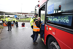© Licensed to London News Pictures. 01/10/2021. London, UK. Protesters being arrested and put on a bus commandeered by police, which was stuck in the traffic.. Climate protest group Insulate Britain block the M1 at the junction with the North Circular at Staples Corner in North London. Insulate Britain have successfully blocked various roads around the capital over a number of weeks, resulting in a court injunction banning them from going near the M25 motorway. Photo credit: London News Pictures