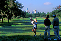 Stock photo of a man swinging to drive his shot down the fairway