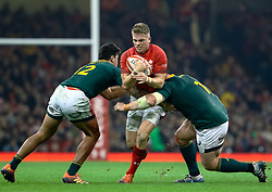 Gareth Anscombe of Wales under pressure from Damian de Allende of South Africa<br /> <br /> Photographer Simon King/Replay Images<br /> <br /> Under Armour Series - Wales v South Africa - Saturday 24th November 2018 - Principality Stadium - Cardiff<br /> <br /> World Copyright © Replay Images . All rights reserved. info@replayimages.co.uk - http://replayimages.co.uk
