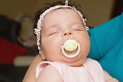 Close up of sleeping baby with dummy in her mouth,