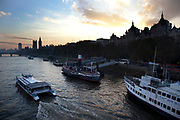 Evening scene as the sun sets looking over the River Thames towards the skyline of Westminster and the Houses of Parliament. London.