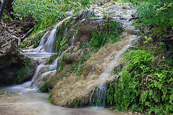 Waterfall on spring-fed stream, with flow amplified by recent rains, Hill Country between Blanco and Fredericksburg, Texas, USA