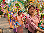 "05 APRIL 2015 - CHIANG MAI, CHIANG MAI, THAILAND: Tai Yai women carry money trees with donations while they lead a parade of Buddhist novices during the second day of the three day long Poi Song Long Festival in Chiang Mai. The Poi Sang Long Festival (also called Poy Sang Long) is an ordination ceremony for Tai (also and commonly called Shan, though they prefer Tai) boys in the Shan State of Myanmar (Burma) and in Shan communities in western Thailand. Most Tai boys go into the monastery as novice monks at some point between the ages of seven and fourteen. This year seven boys were ordained at the Poi Sang Long ceremony at Wat Pa Pao in Chiang Mai. Poy Song Long is Tai (Shan) for ""Festival of the Jewel (or Crystal) Sons.    PHOTO BY JACK KURTZ"