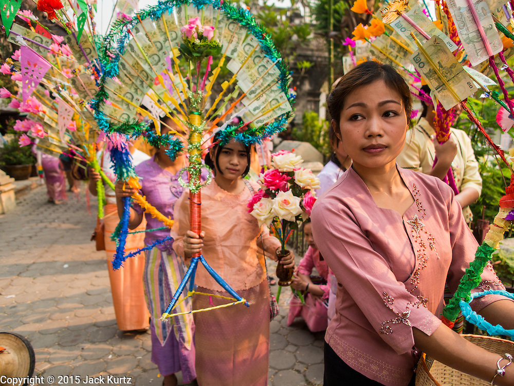 """05 APRIL 2015 - CHIANG MAI, CHIANG MAI, THAILAND: Tai Yai women carry money trees with donations while they lead a parade of Buddhist novices during the second day of the three day long Poi Song Long Festival in Chiang Mai. The Poi Sang Long Festival (also called Poy Sang Long) is an ordination ceremony for Tai (also and commonly called Shan, though they prefer Tai) boys in the Shan State of Myanmar (Burma) and in Shan communities in western Thailand. Most Tai boys go into the monastery as novice monks at some point between the ages of seven and fourteen. This year seven boys were ordained at the Poi Sang Long ceremony at Wat Pa Pao in Chiang Mai. Poy Song Long is Tai (Shan) for """"Festival of the Jewel (or Crystal) Sons.    PHOTO BY JACK KURTZ"""