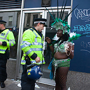 A carnival performer dressed in green talks to a police officer in riot gear in Portobello Road.The Notting Hill Carnival has been running since 1966 and is every year attended by up to a million people. The carnival is a mix of amazing dance parades and street parties with a distinct Caribbean feel.