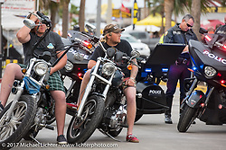 A couple of bikers get pulled over by two local Motor police on Main Street during Daytona Beach Bike Week. FL. USA. Sunday March 12, 2017. Photography ©2017 Michael Lichter.