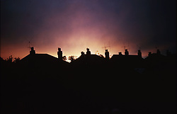 Rooftops of houses viewed as silhouettes against sunset,