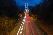 Traffic flowing through the Stanley Park Causeway and onto the Lions Gate Bridge in Vancouver, British Columbia, Canada. The Lions Gate Bridge was opened in 1938 and is officially known as First Narrows Bridge. The Lions Gate has been a National Historic Site of Canada since 2005.