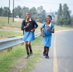 1 March 2017, Thaba Bosiu, Lesotho: Girls on the way to Thaba Bosiu Primary School, a public school accommodating some 100 children in Thaba Bosiu, Lesotho. To the left, Mokho, and to the right, Khodliso. Thaba Bosiu is a sandstone plateau some 24 kilometers east of Lesotho's capital, Maseru. The name means Night Mountain, and surrounding the plateau is a small village and open plains. Thaba Bosiu was once the capital of Lesotho, and the mountain was the stronghold of the Basotho king when the kingdom of Lesotho was formed.