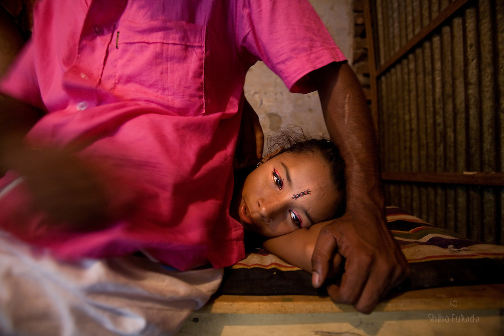 Sex worker Nodi,14, lies down by  a customer at brothel in Tangail, Bangladesh. Nodi run away from home after falling in love with a Hindu boy and ended up in the brothel with her sister.<br /> The majority of the 20,000 to 30,000 female sex workers in Bangladesh are victims of trafficking. <br /> Once they enter the brothel, usually before the age of 12, they are generally in for life because of social stigma and poverty.