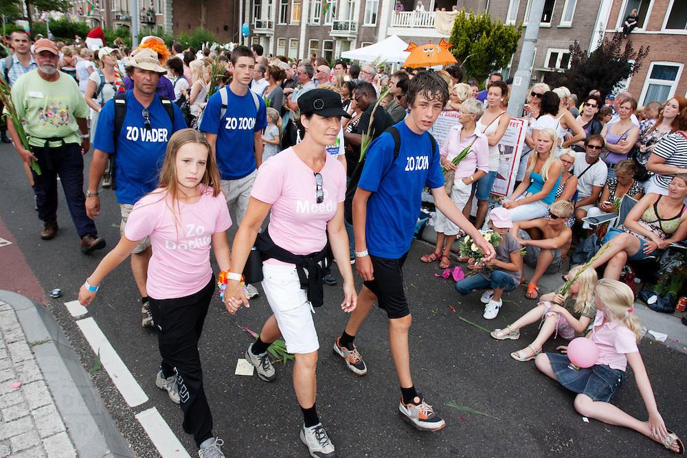 Een gezin loopt de laatste kilometers van de Nijmeegse Vierdaagse over de Via Gladiola, zoals de Sint Annastraat heet tijdens het wandelevenement