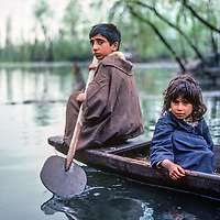 A brother and sister paddle a shikar boat on Dal Lake, Srinigar, Kashmir, India.