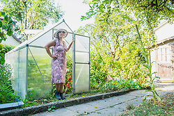 Senior woman in a garden with greenhouse, Altoetting, Bavaria, Germany