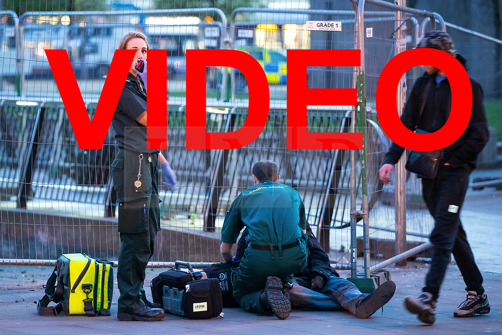 VIDEO available here: https://we.tl/zvcu9ewaJi<br /> <br /> © Licensed to London News Pictures . 07/04/2017 . Manchester , UK . Paramedics helping a man , lying collapsed on the pavement on Piccadilly Gardens . Greater Manchester Police have authorised dispersal powers and say they will ban people from the city centre for 48 hours , this evening (7th April 2017) , in order to tackle alcohol and spice abuse . Photo credit : Joel Goodman/LNP