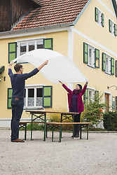 Mid adult couple spreading a tablecloth on the table in front of house, Bavaria, Germany