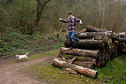 A 14 year-old teenage boy jumps down off a pile of logs during a countryside walk with his pet dog. After running along the tops of the logs, being stored by a local landowner on a countryside path, the lad balances on the timber as he descends to the ground again. His dog is a muddy terrier cross who relishes the outing as much as the boy who is demonstrating a sense of adventure and boyhood in the great outdoors.