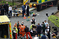 Conservative MP Tobias Ellwood (bottom right) stands amongst the emergency services at the scene outside the Palace of Westminster, London, after policeman has been stabbed and his apparent attacker shot by officers in a major security incident at the Houses of Parliament.