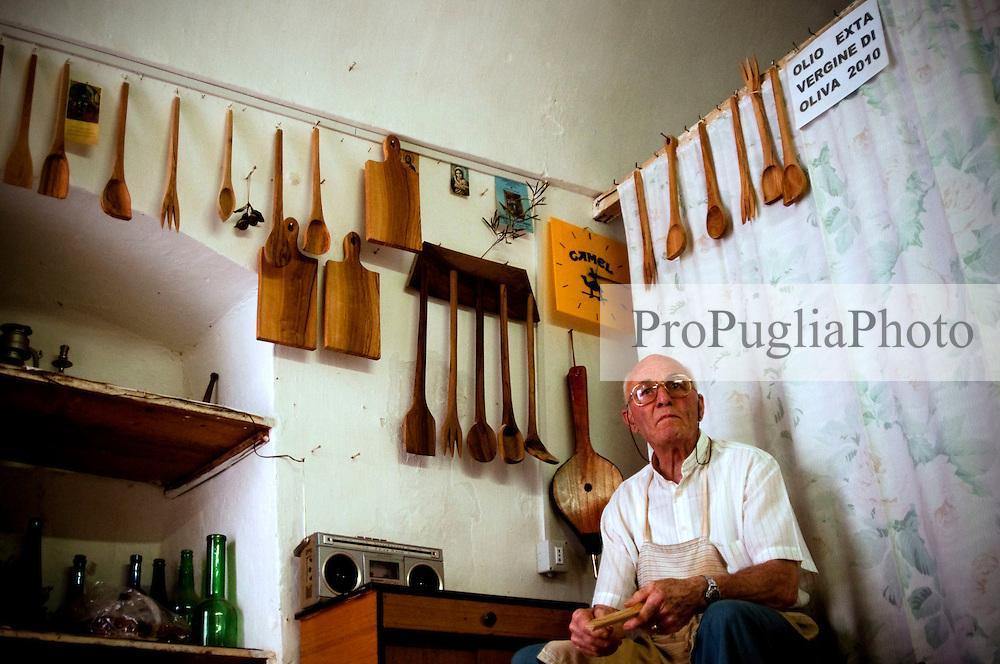 """Laboratorio in cui l'artigiano lavora il legno di ulivo per ottenere utensili da cucina. In alto a destra il cartello indica che si vende olio """"exta"""" vergine d'oliva."""