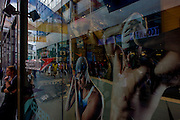 A smoker pauses to enjoy a cigarette below two athletic people chosen to endorse the Speedo brand, in a window at the Westfield mall during the London 2012 Olympics, the 30th Olympiad. Ironicvally juxtaposed together, we see the healthy specimens of the two athletes with fine bodies in Speedo swimwear contrasting the bad connotations of smoking and ill-health. Smoking kills around 120,000 people in the UK each year and with current smoking trends, about 500 million people alive today will eventually be killed by tobacco use. The international swimwear brand, which sponsors British Swimming and Olympic gold medallist Rebecca Adlington as well as Multi-medallist Michael Phelps.