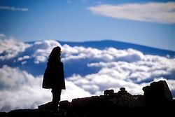 tourist at the peak of Mauna Kea volcanic mountain, looking out the summit of Mauna Loa, Big Island, Hawaii
