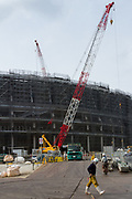 Workmen in front of cranes at the construction site for the new main stadium for the 2020 Tokyo Olympics in Gaiemmae, Tokyo, Japan Tuesday June 26th 2018. After many delays the main stadium construction is expected to be finished by November 2019. The Tokyo 2020 Olympics will take place from July 24th to August 9th  2020
