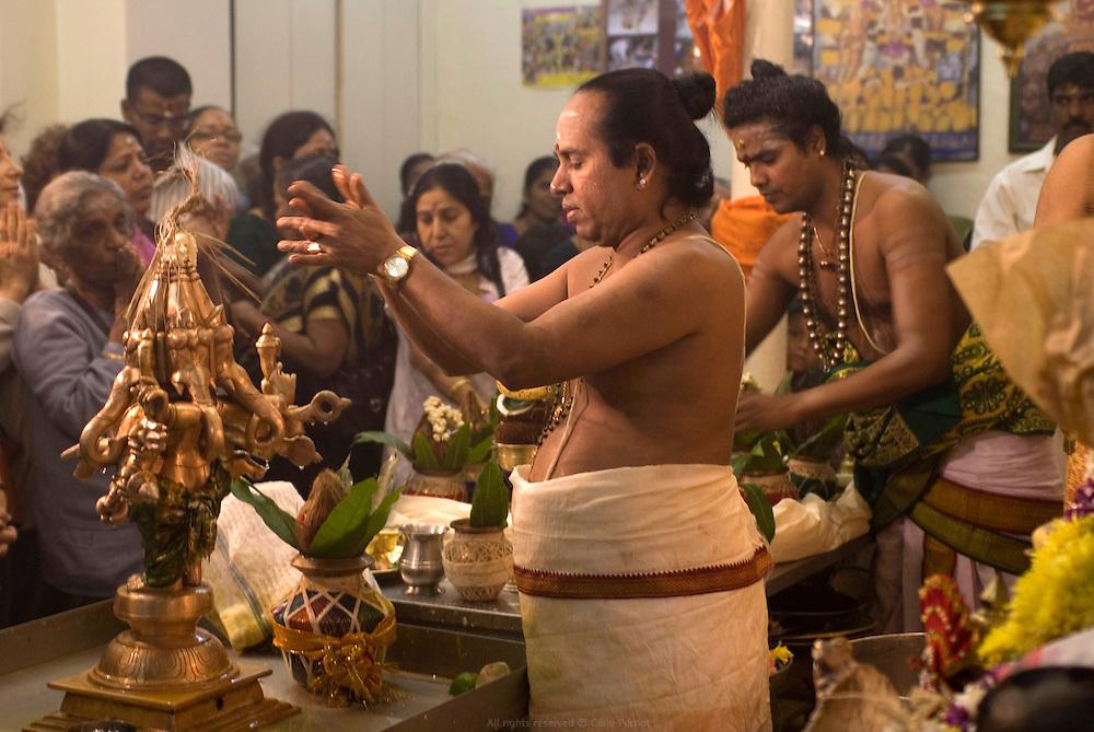 Cérémonie Puja au Temple Sri Manicka Vinayakar Alayam dédié à Ganesh, le Dieu à tête d'éléphant. Les prêtres, brahmanes du sud de l'Inde, récitent des mantras en sanscrit, versent des offrandes de fleurs, de fruits, de lait et de miel sur les statuts des Dieux présentes dans le temple puis, les purifient par le feu.<br /> <br /> Puja ceremony at Sri Manicka Vinayakar Alayam Temple, dedicated to Ganesh, the god with an elephant head.