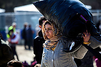 MYTILINI, GREECE - FEBRUARY 09: A woman carries her belonging over her head after arriving at the Moria refugee camp with dozens of refugees on February 09, 2015 in Mytilini, Greece. After travelling for more than two hours crossing the Aegean sea, refugees are picked up by buses run by UNHCR and transferred to the Moria refugee camp where they have to register their names. As thousands of refugees arrive everyday in Lesvos, queues for registration can take up to two days. In the camp several international organisations provide assistance to the refugees as food, medical assistance, blankets and clothes among other items and services. Photo: © Omar Havana. All Rights Are Reserved