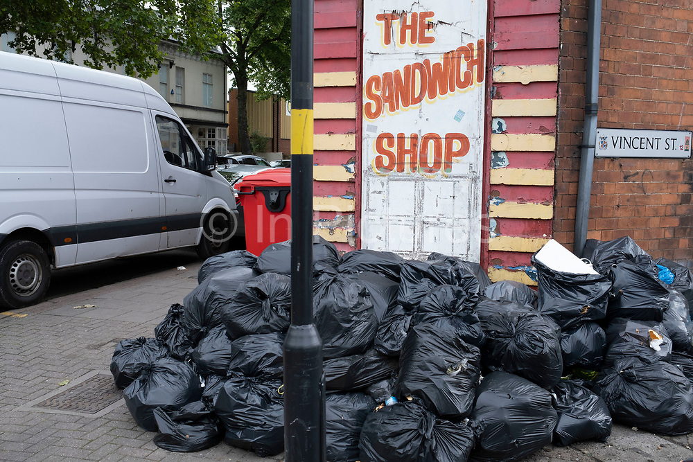 Rubbish bags left outside a sandwich shop on a street corner in Highgate on 9th June 2020 in Birmingham, United Kingdom. In this area of Birmingham, there is a huge problem with the lack of rubbish collection and litter cleaning by Birmingham City Council which local people say do not collect the waste from small businesses anywhere nearly regularly enough.