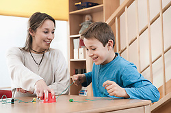 Portrait of playing boy and female childcare assistant