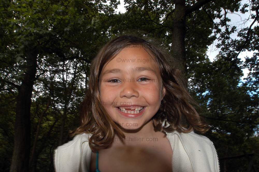 smiling 6 year old girl with large gaps in teeth