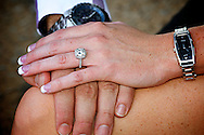 Grooms hand on his brides leg with her hand on his showing over her diamond engagement ring